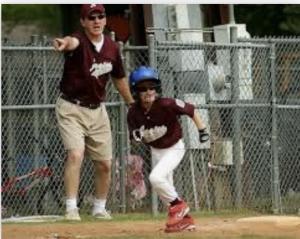 Little League Coach Guiding Baserunner